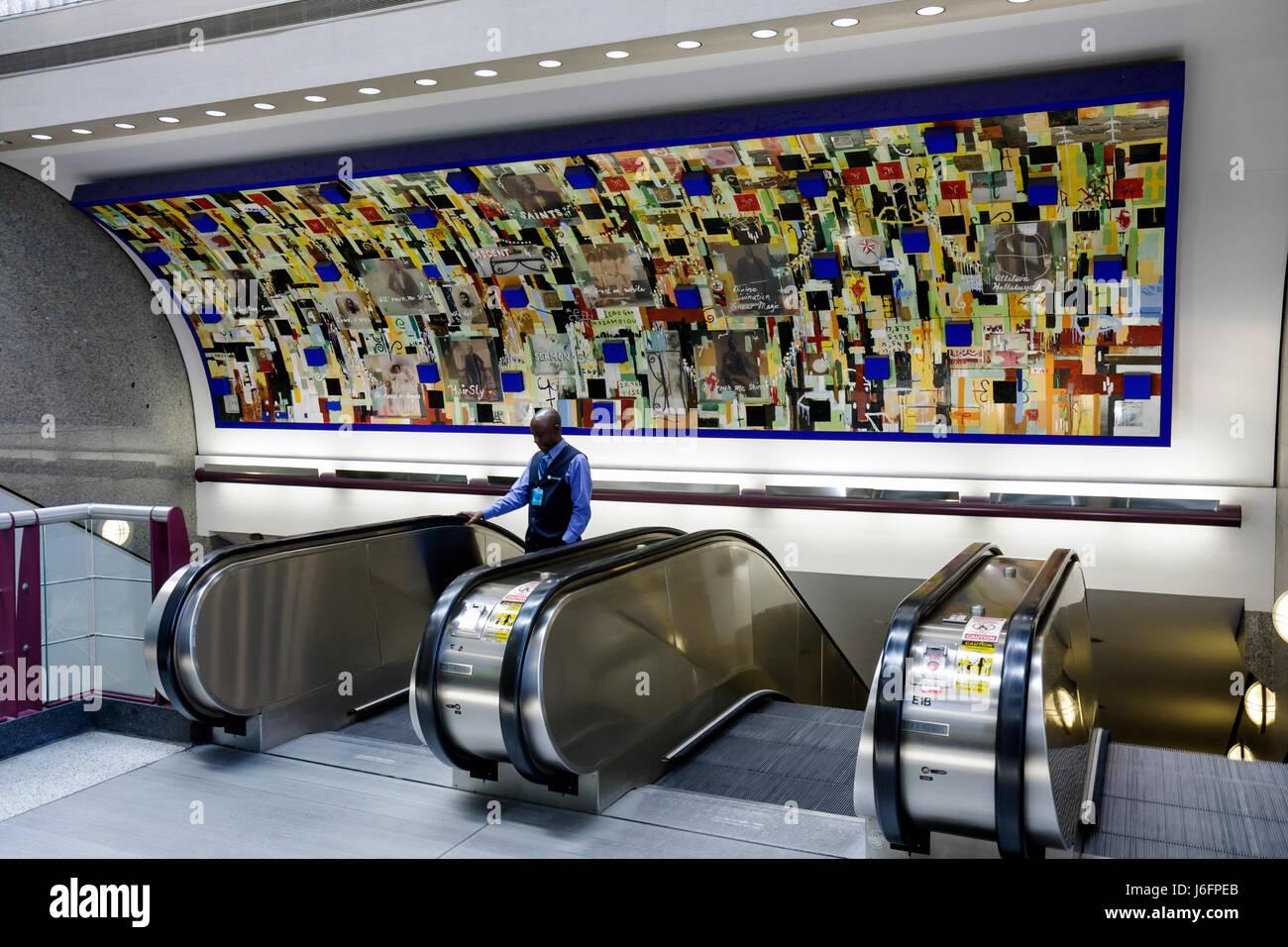 Atlanta Georgia Hartsfield-Jackson Atlanta International Airport escalator up down mural public art Black man Saints - Stock Image
