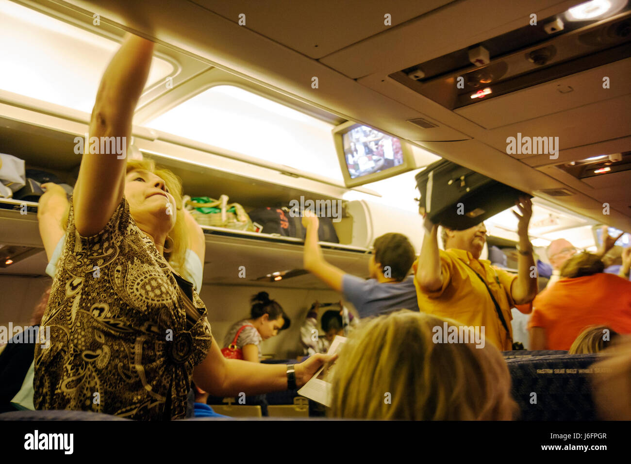 Chicago Illinois O'Hare International Airport American Airlines woman man passenger jet aisle overhead compartment - Stock Image