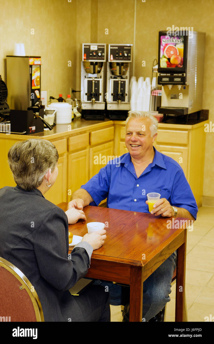 Tennessee Sevierville Oak Tree Lodge man woman couple hold hand senior hotel continental breakfast dining room table - Stock Image