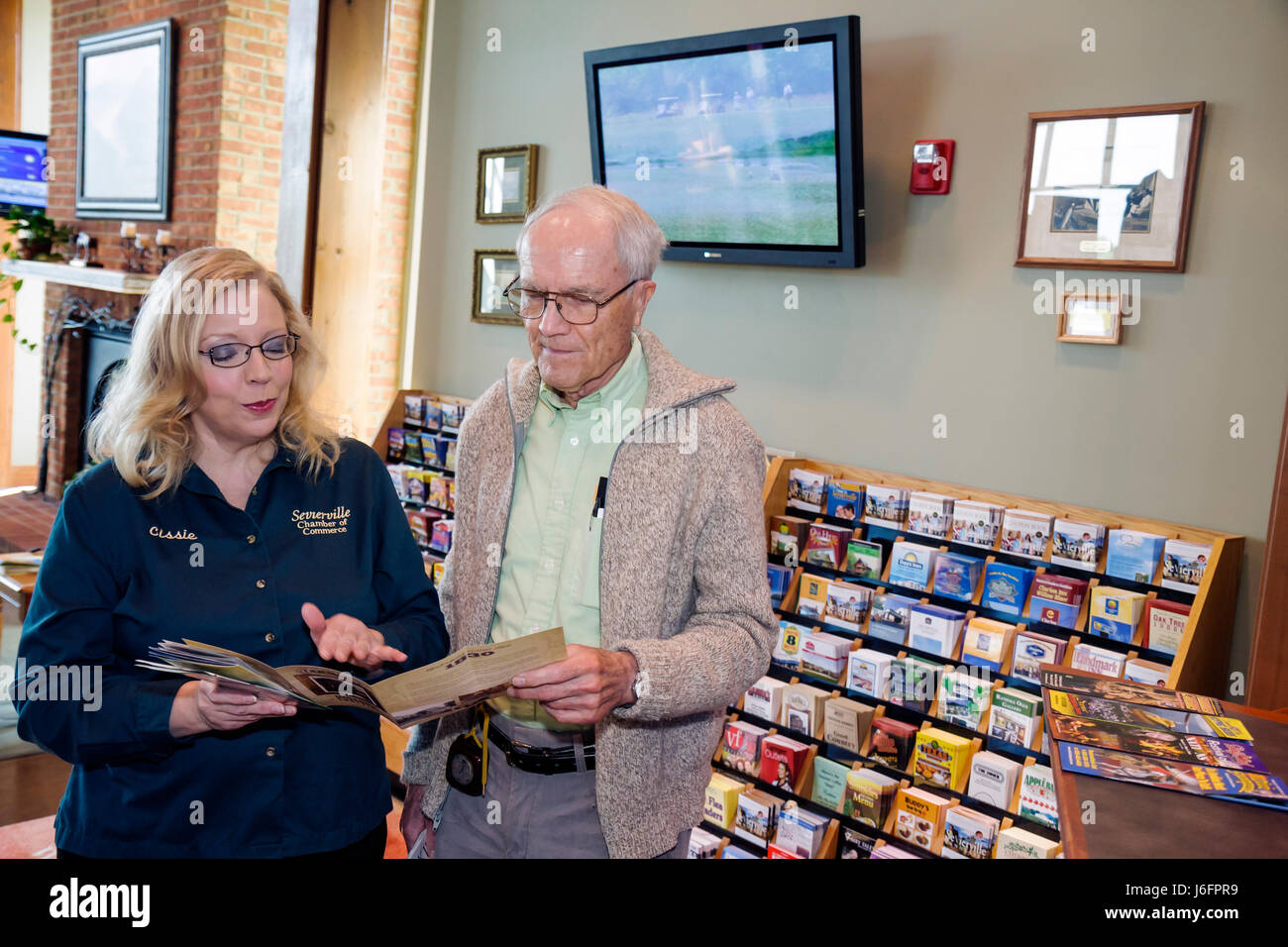 Tennessee Sevierville Chamber of Commerce Visitor Center woman man senior helper greet welcome information assist - Stock Image