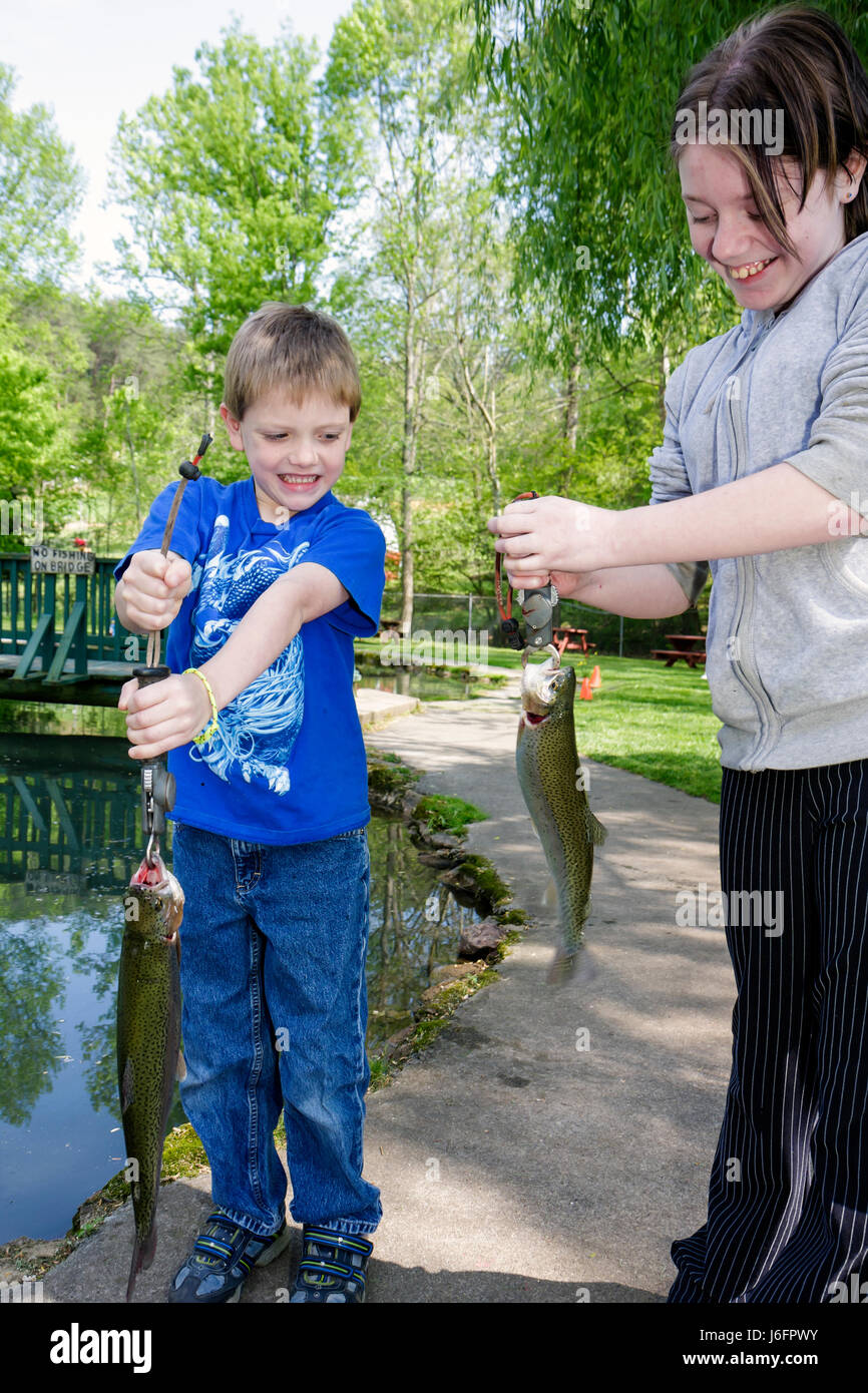 Tennessee Sevierville English Mountain Trout Farm and Grill catch eat rainbow trout boy girl sister brother family - Stock Image