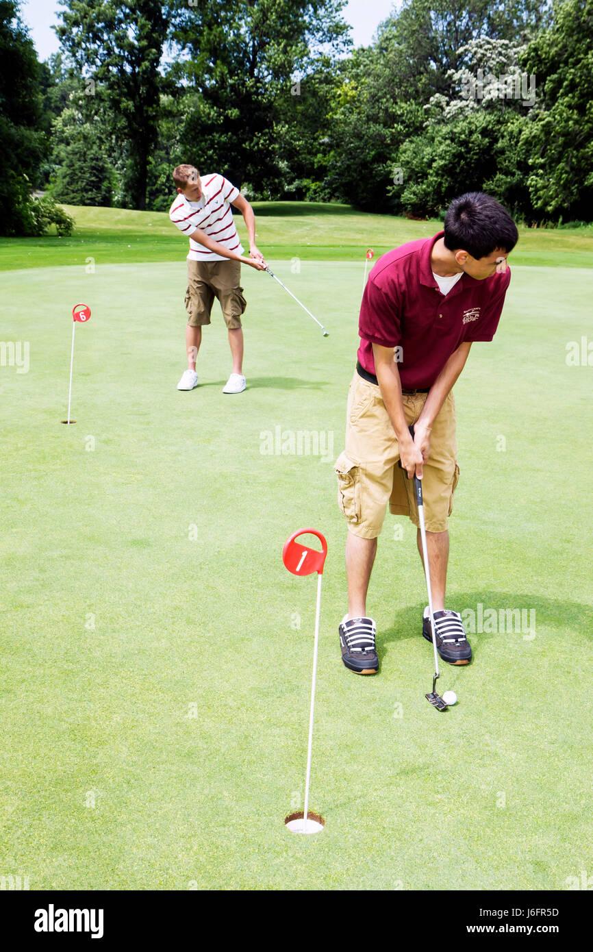 Wisconsin Kenosha Kansasville Brighton Dale Links golf course county park system practice green boy teen boy putter - Stock Image