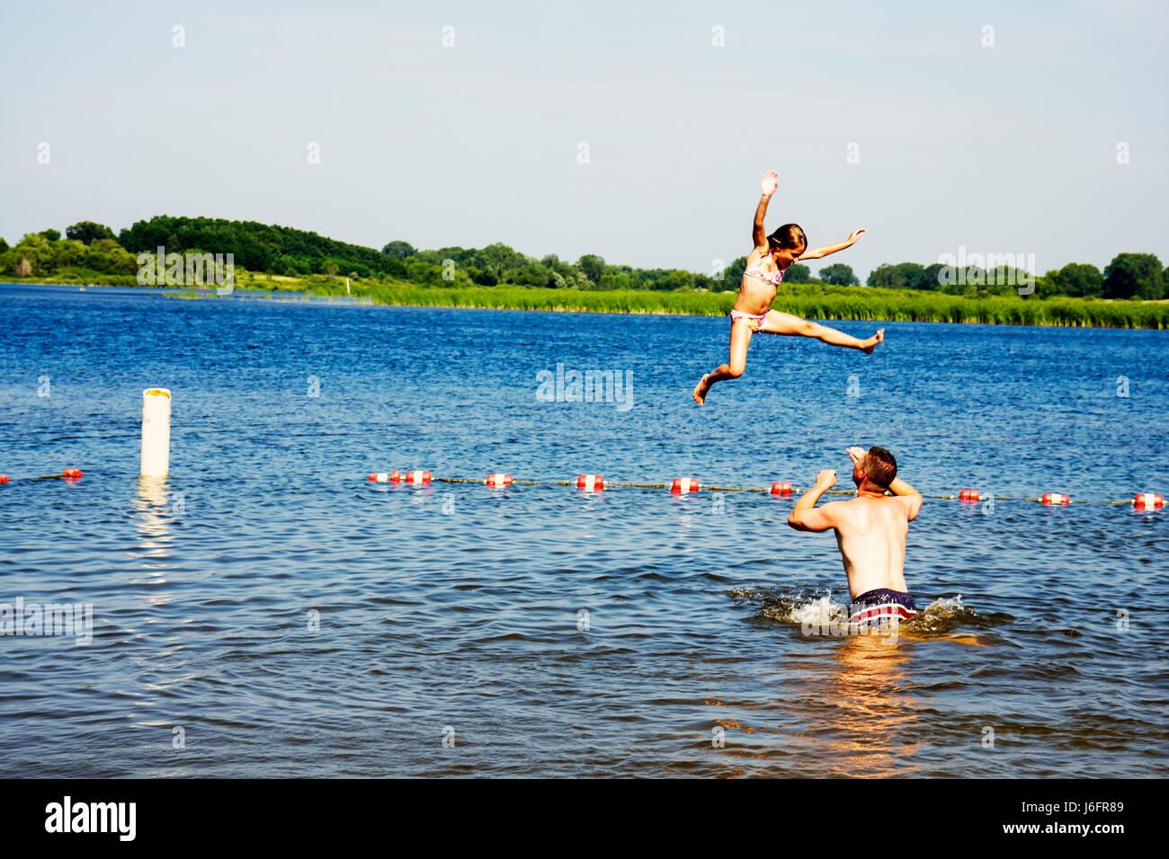 Wisconsin Kenosha Kansasville Richard Bong State Recreation Area Wolf Lake beach man girl parent father kid splash - Stock Image