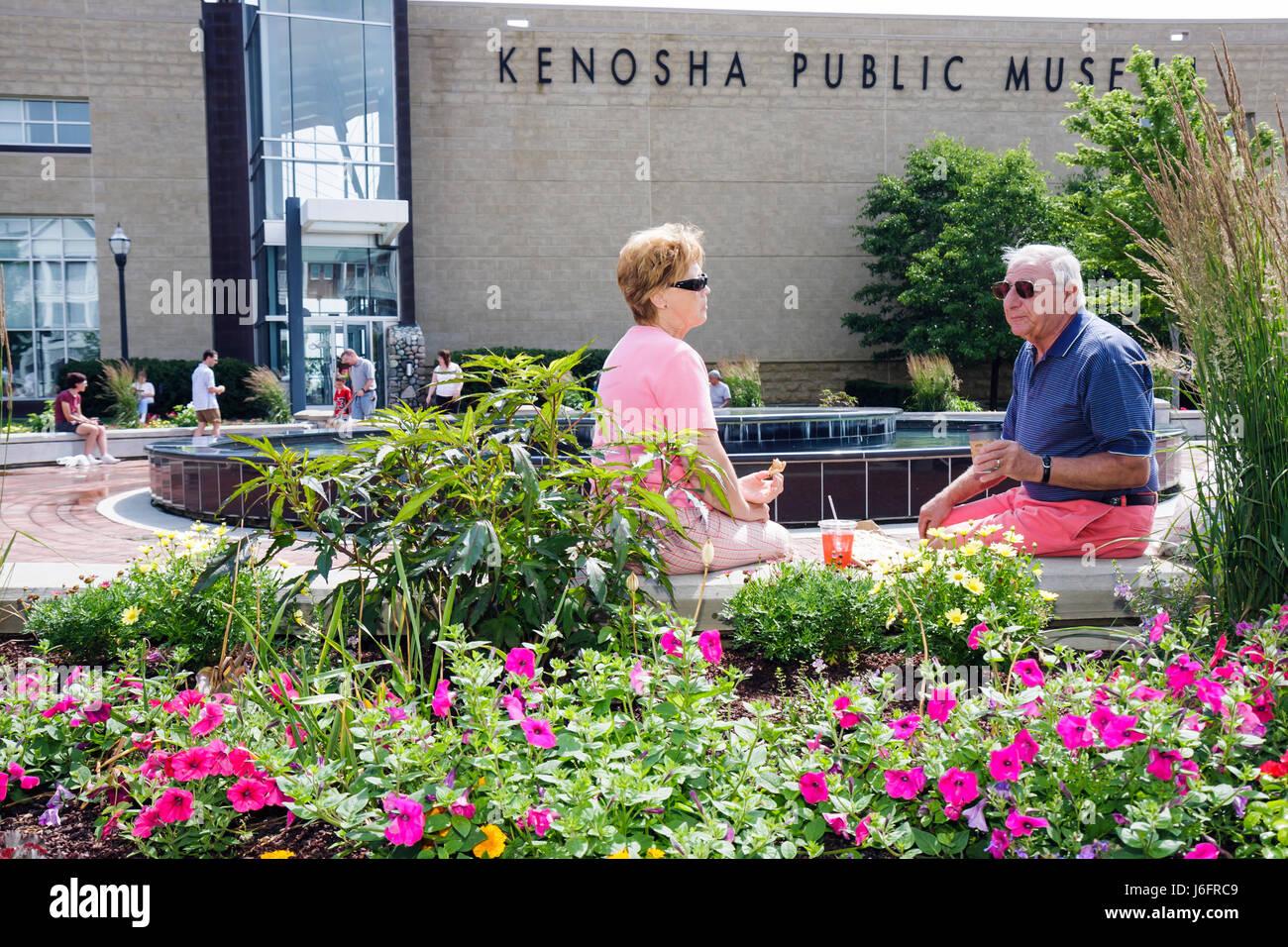 Wisconsin Kenosha Kenosha Public Museum man woman couple picnic flowers garden plaza summer - Stock Image