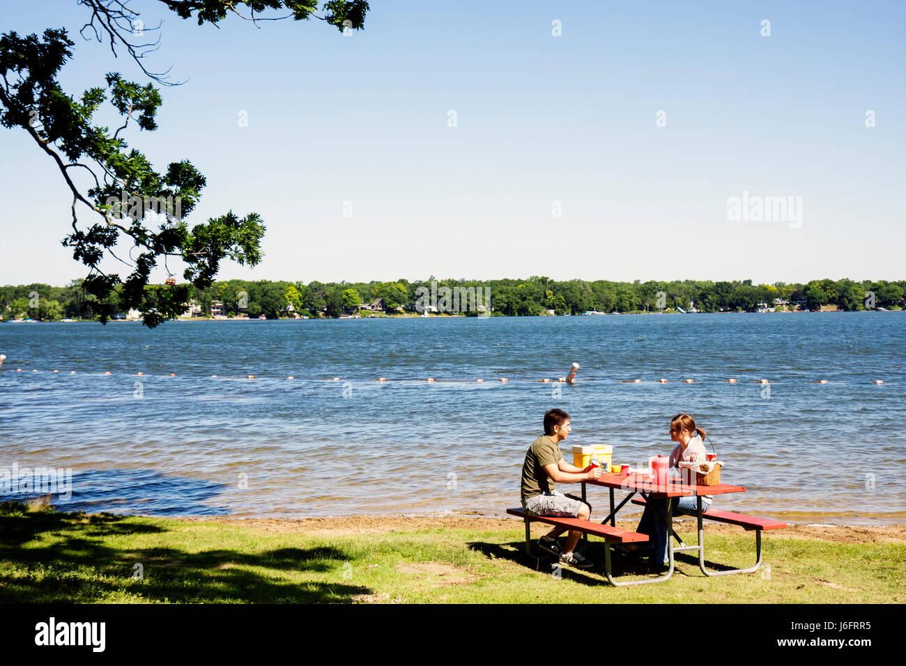 Wisconsin Kenosha Paddock Lake Old Settlers Park Asian man woman couple picnic bench lakeshore outdoor recreation - Stock Image