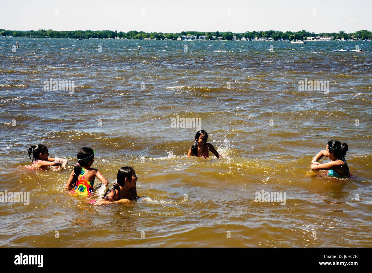 Wisconsin Kenosha Silver Lake Silver Lake Park Hispanic girls swim splash summer vacation fun beach play - Stock Image