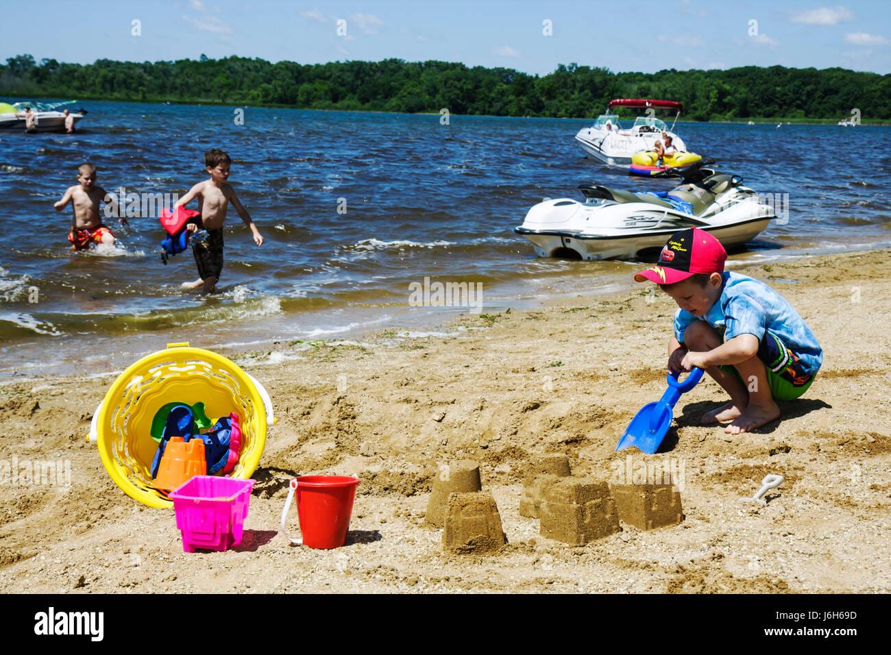 Wisconsin Kenosha Silver Lake Silver Lake Park boy summer vacation play beach sand pail bucket shovel toys boat - Stock Image