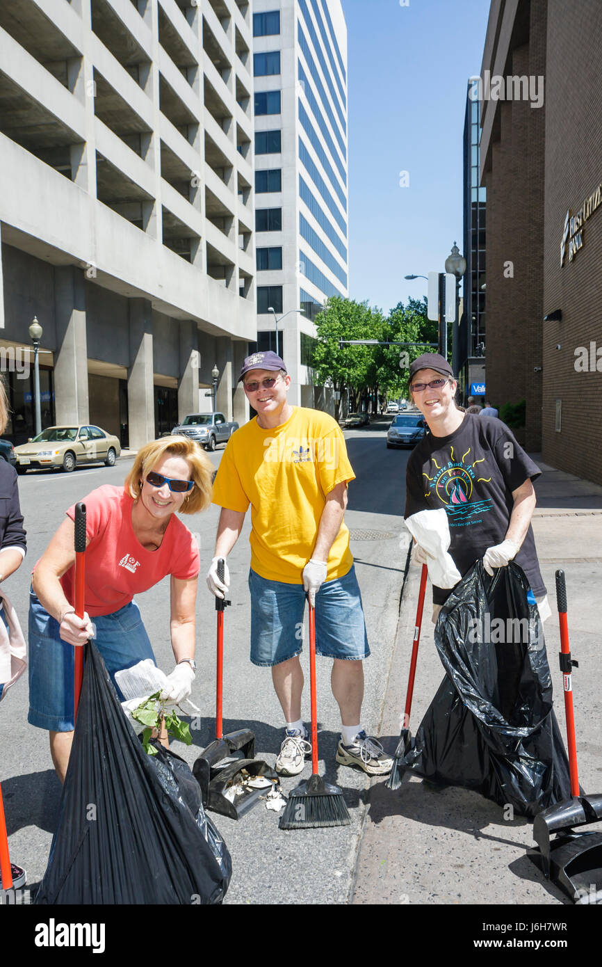Virginia Roanoke Church Street Clean up Day volunteers man woman women sweep trash bags community service - Stock Image