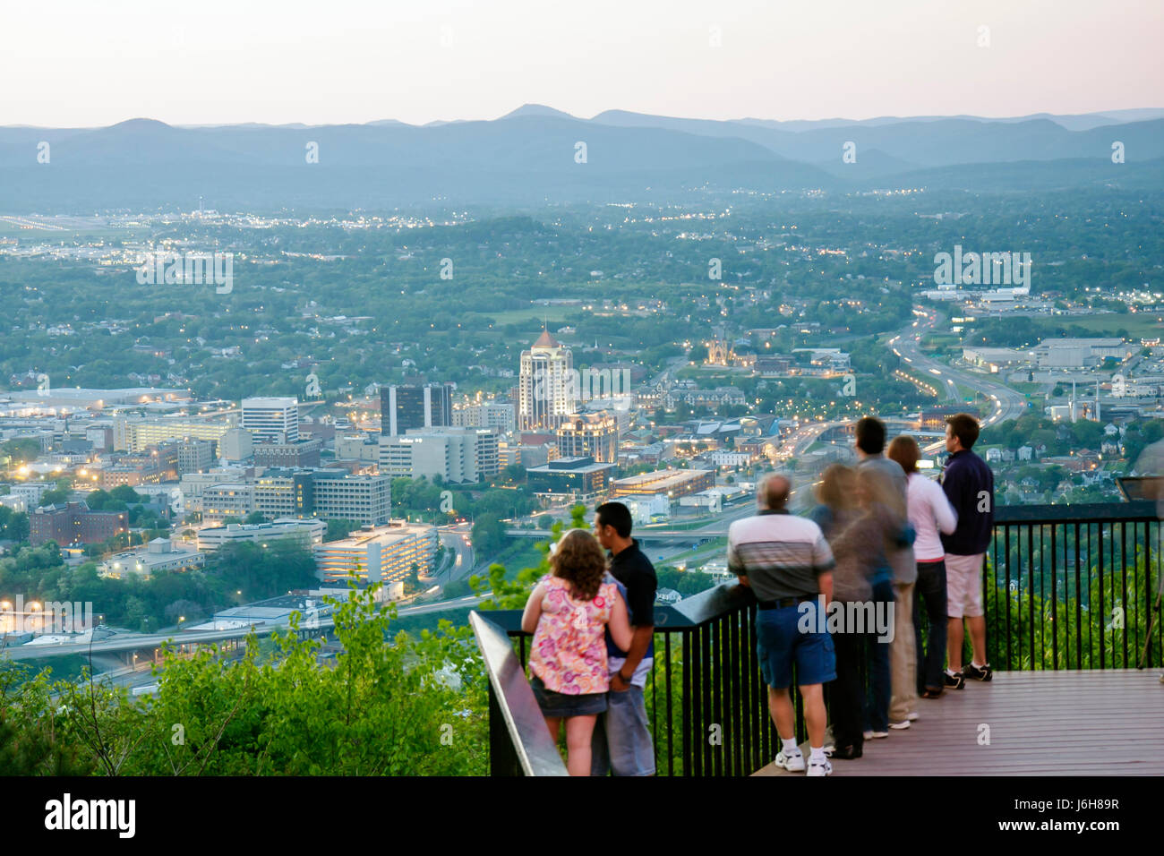 Virginia Roanoke Mill Mountain Overlook man woman couple families view downtown city dusk evening Allegheny Mountains - Stock Image