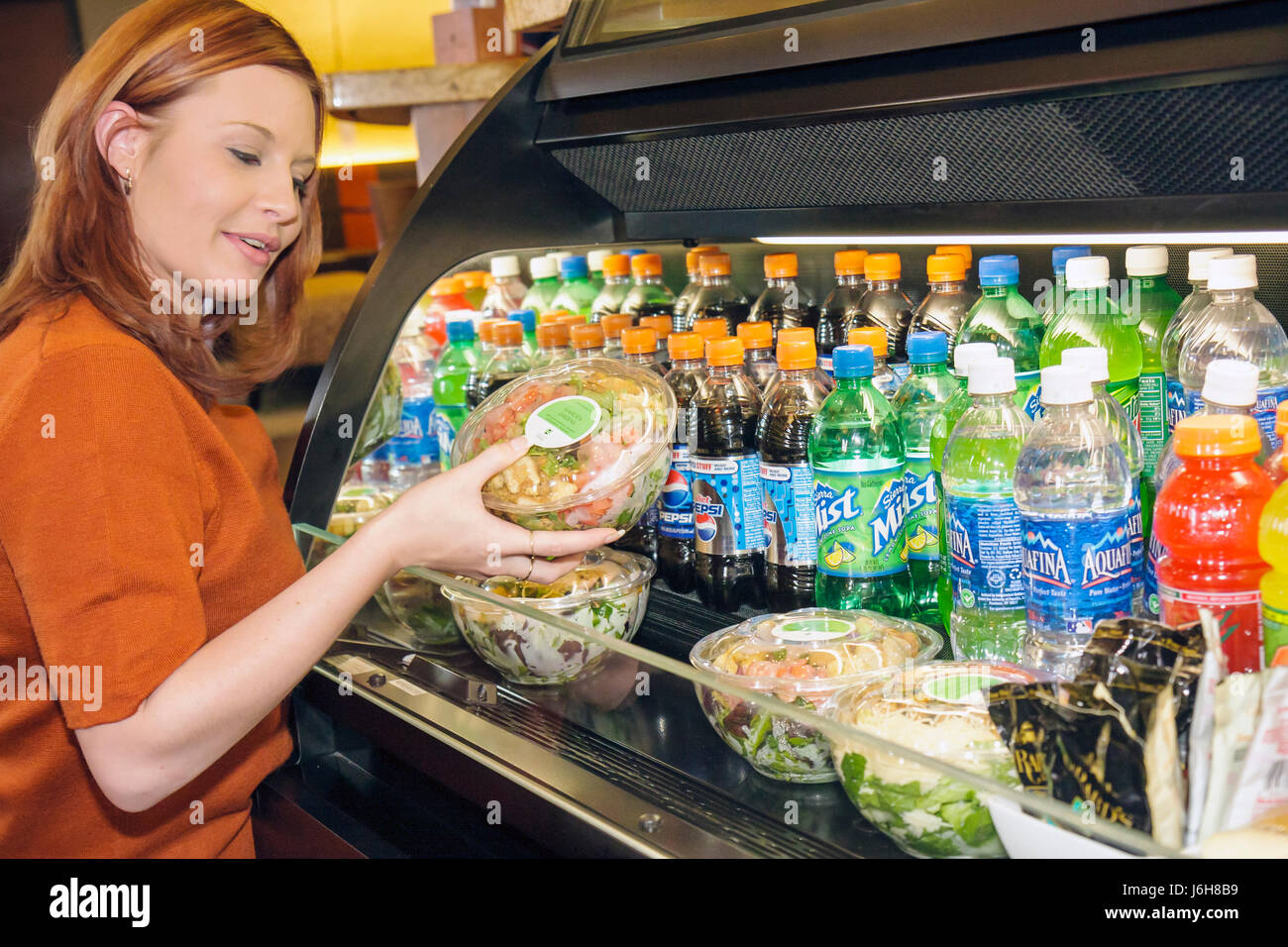 Virginia Roanoke Hyatt Place lobby hotel woman Cherokee Native American selects salad food refrigerated bottles - Stock Image