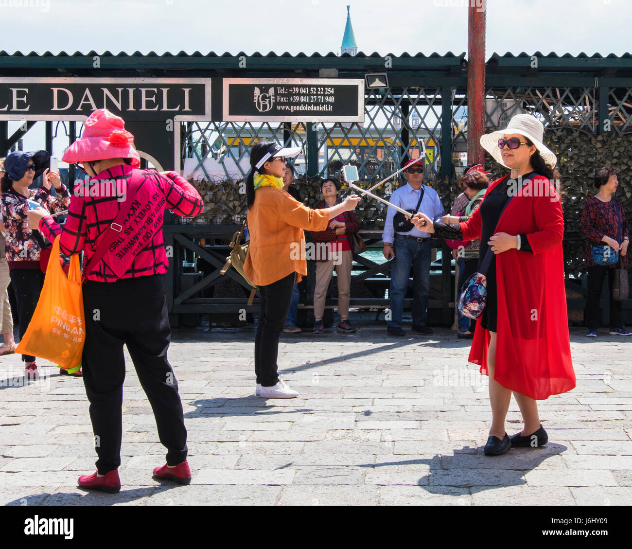 Venice, Italy. Colourfully dressed women tourists take selfies using selfie sticks after arriving at the tourist - Stock Image