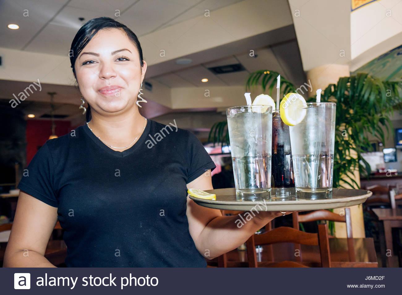 Miami Florida Miami Lakes Main Street Italy Today Restaurant Hispanic female woman waitress service water - Stock Image