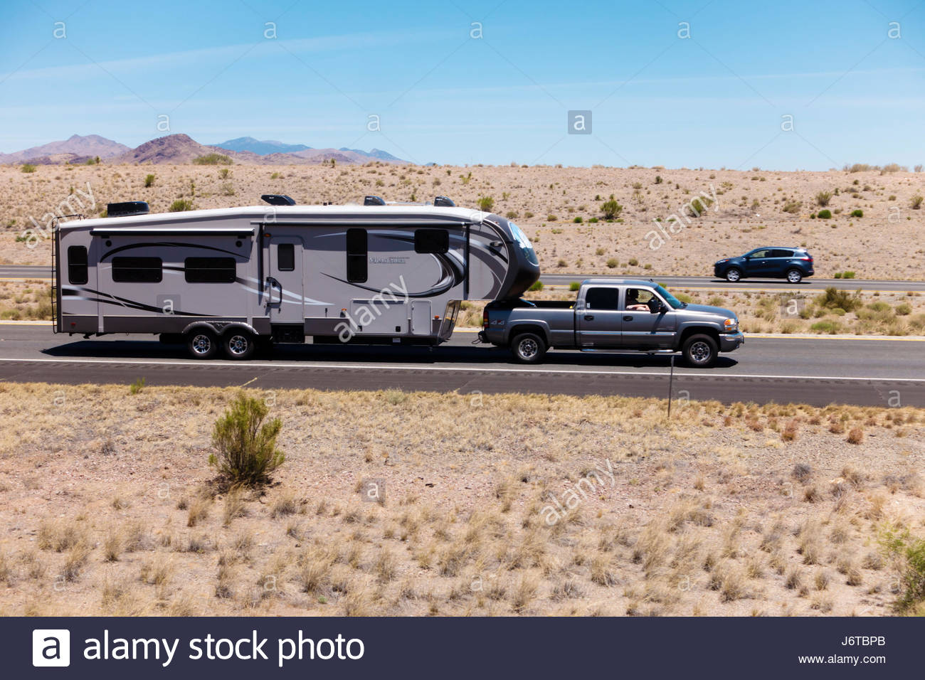 Pickup towing fifth wheel travel trailer on I-10 in southeastern Arizona 3 people visible - Stock-Bilder