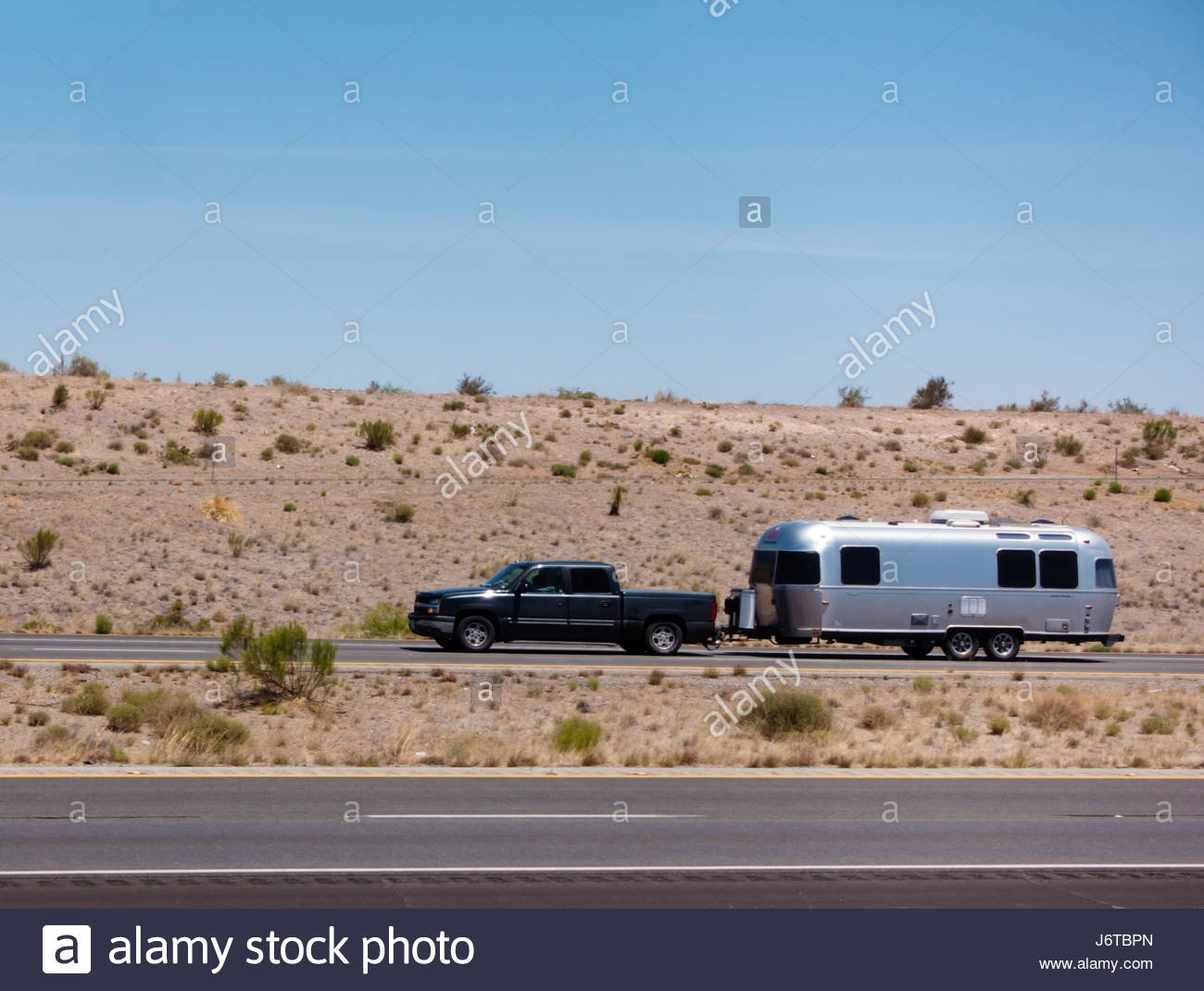Pickup towing travel trailer on I-10 in southeastern Arizona one person visible - Stock-Bilder