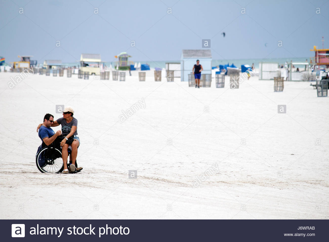 Miami Beach Florida public beach wheelchair disabled man woman - Stock Image