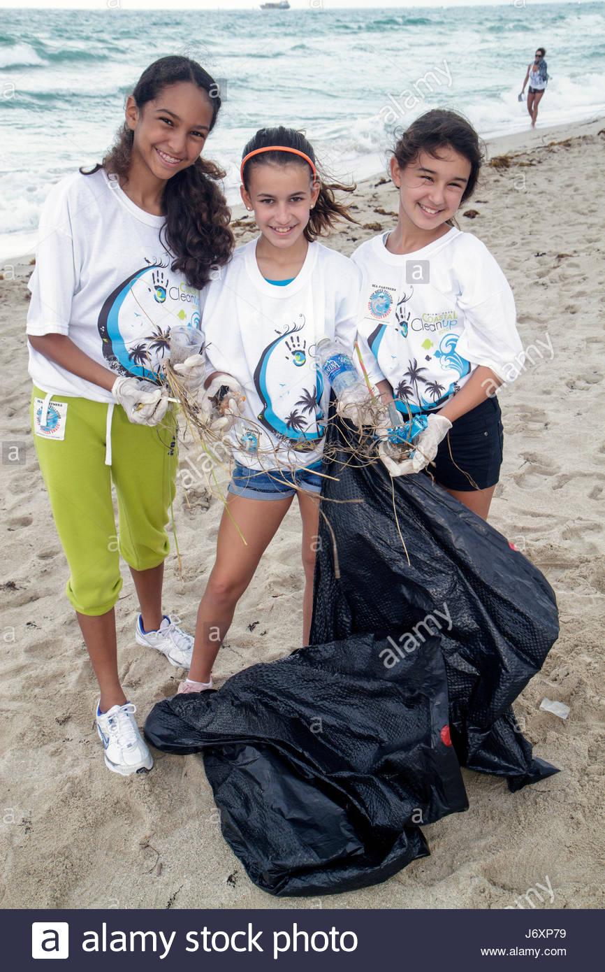 Miami Beach Florida Coastal Cleanup Day volunteer litter trash pollution student public beach pick up Black Hispanic - Stock Image