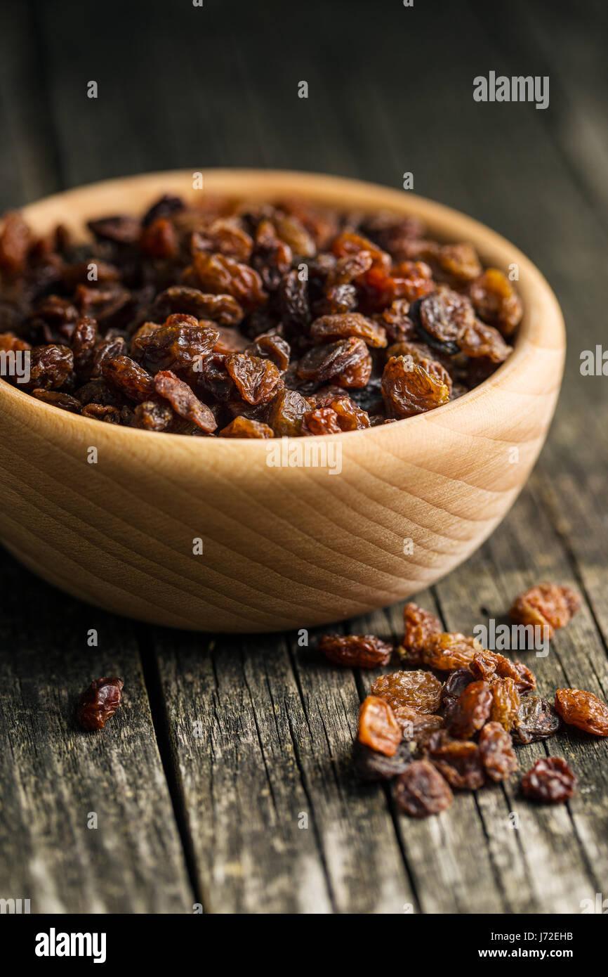 Sweet dried raisins in bowl. - Stock Image
