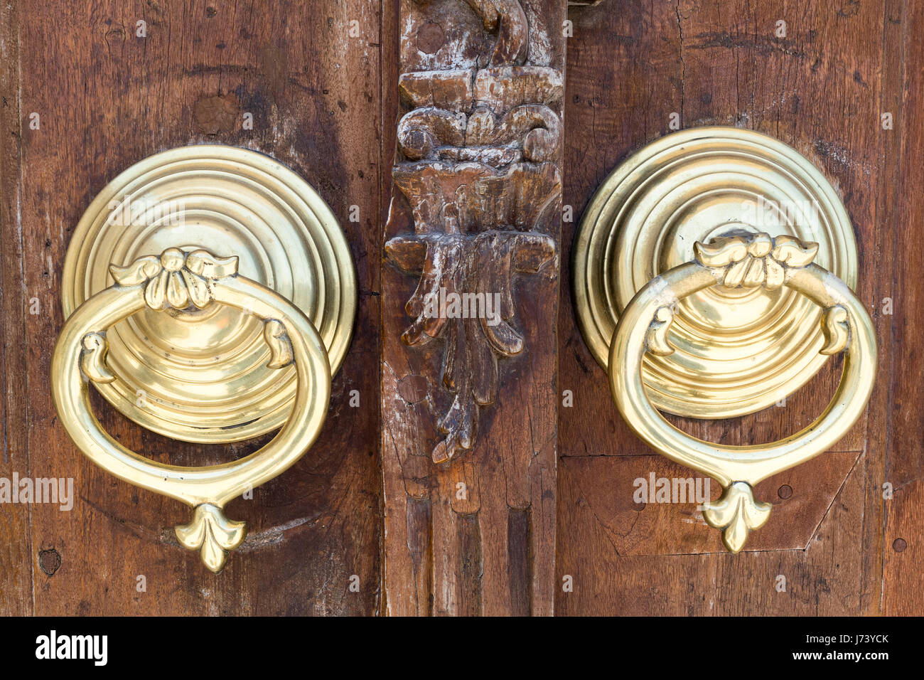 Closeup of two antique copper ornate door knockers over an aged wooden ornate door, Fatih Mosque, Istanbul, Turkey - Stock Image