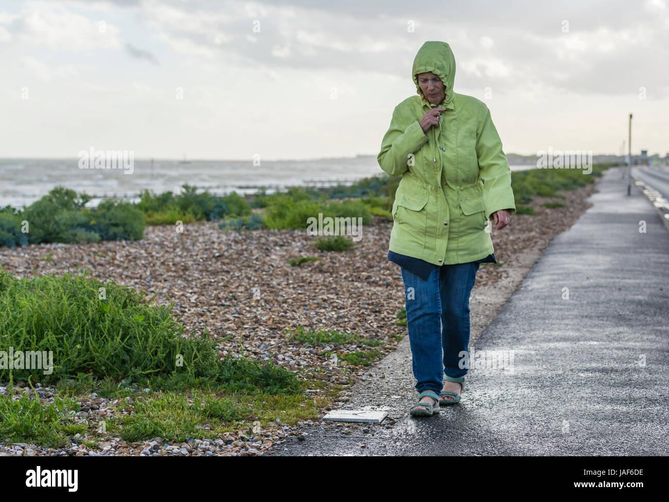 elderly-woman-walking-in-rain-and-wind-a