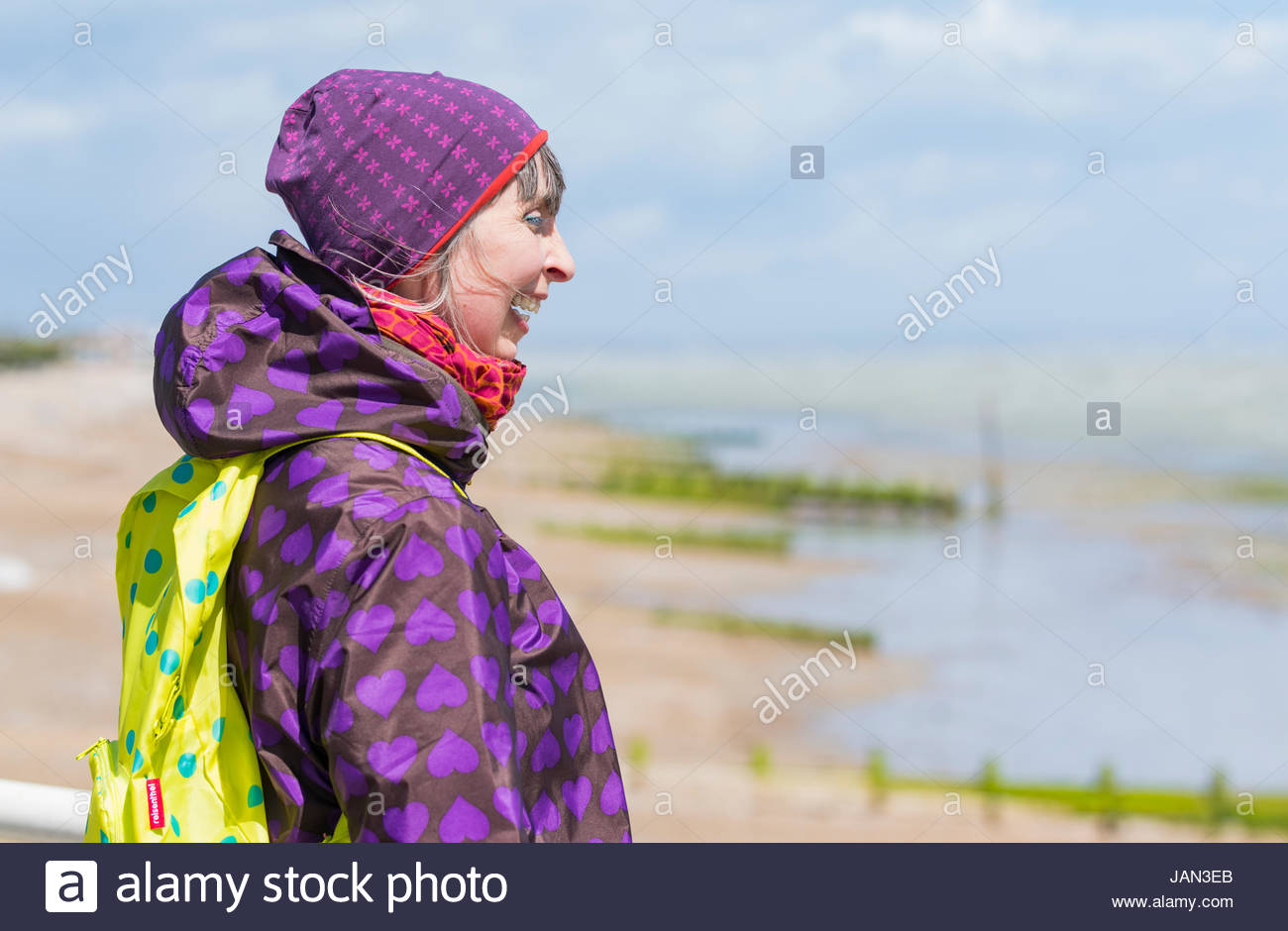 woman-dressed-in-a-hat-and-coat-on-a-windy-dull-day-at-the-seaside-JAN3EB.jpg