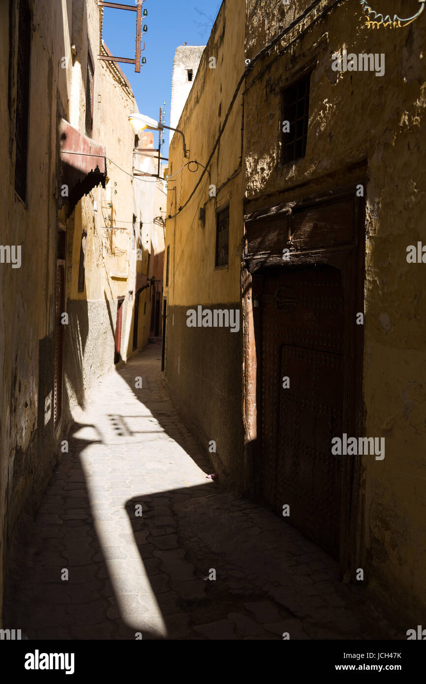 Harsh sun and shadows fall in a narrow alleyway between traditional houses in Meknes, Morocco Stock Photo