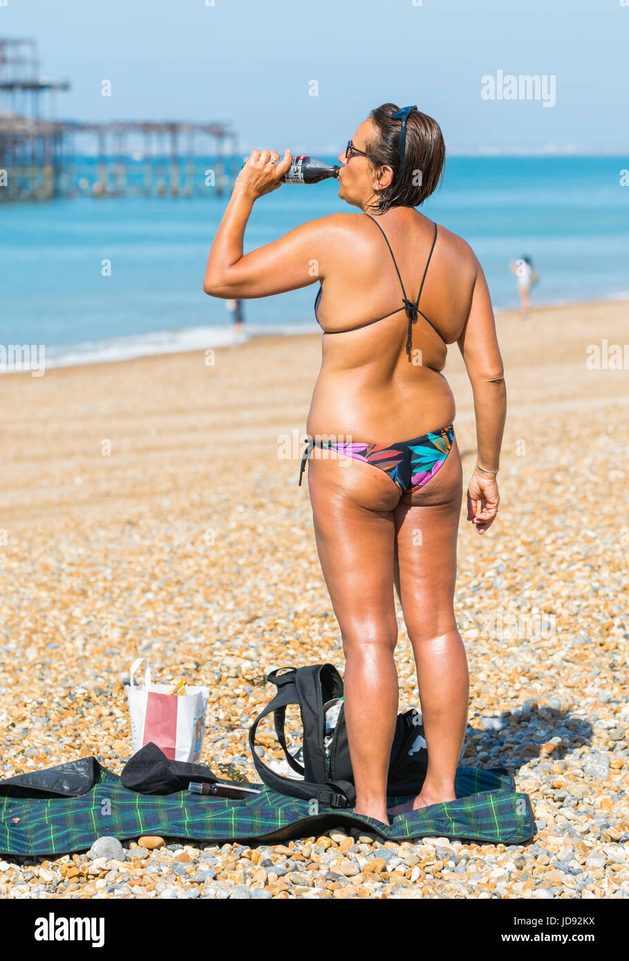 summer-concept-summer-drink-very-tanned-woman-in-bikini-having-a-drink-JD92KX.jpg