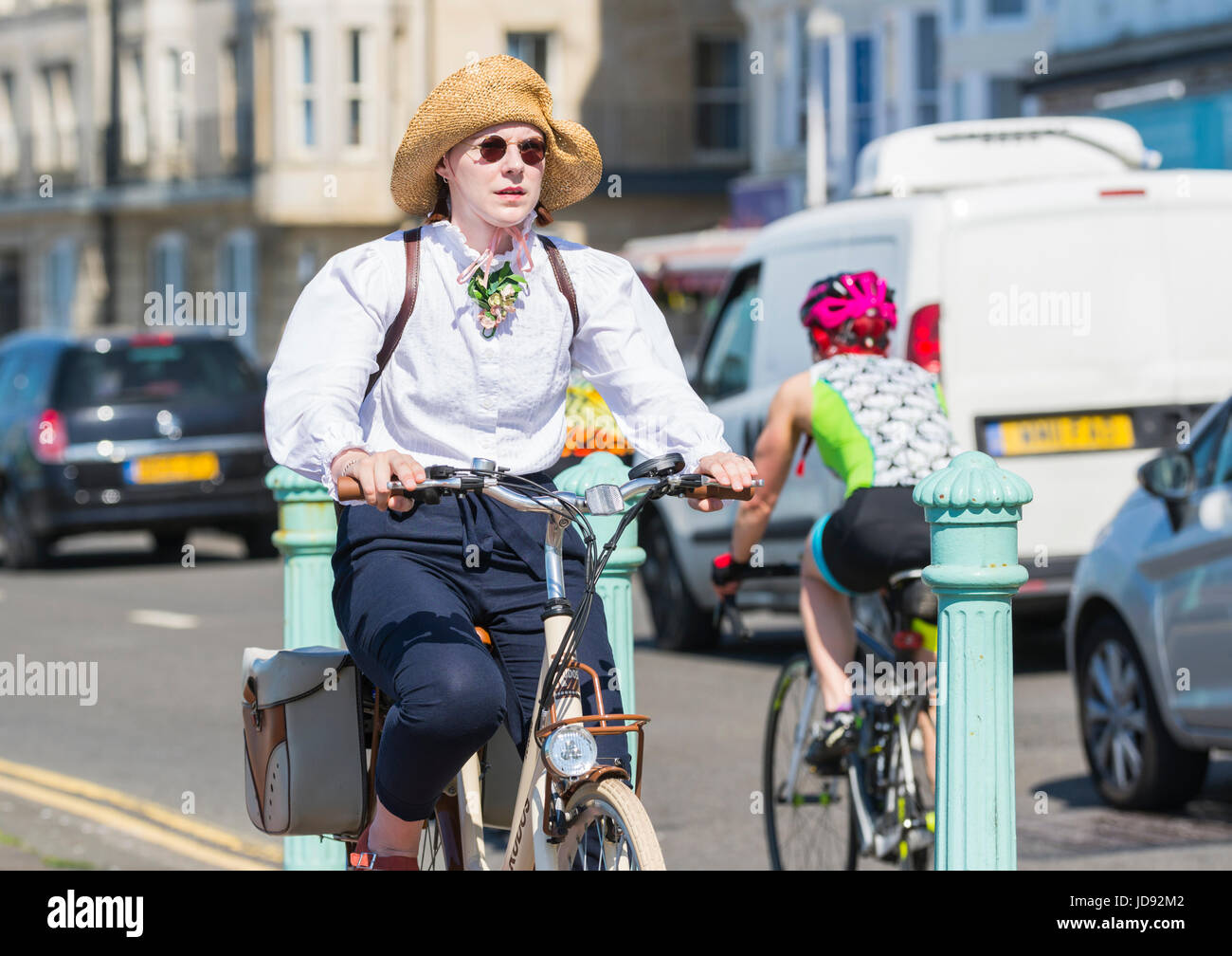 Lady cycling along a cycle lane in Summer, wearing a Summer hat. Stock Photo