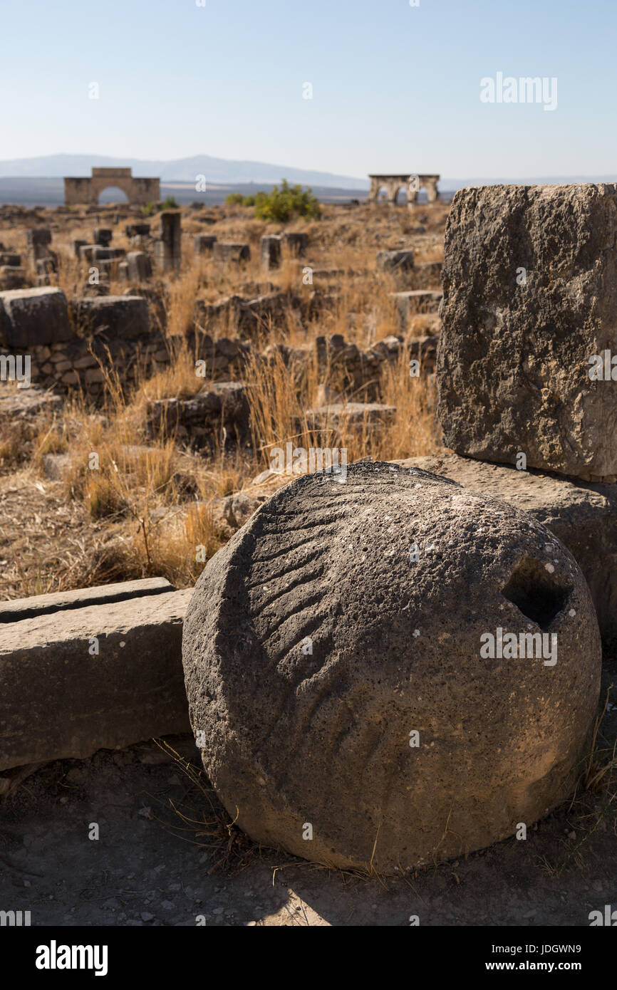 A large carved stone, possibly part of a mill, lies against a wall in the ruined Roman rown of Volubilis in Morocco Stock Photo
