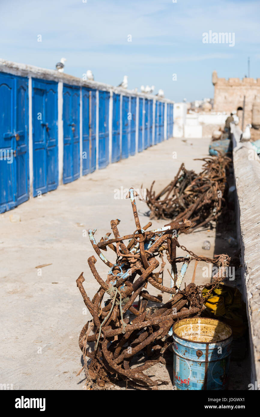 Rusty anchors lie by the side of a path with blue lockers for the fishermen in Essaouira, Morocco Stock Photo