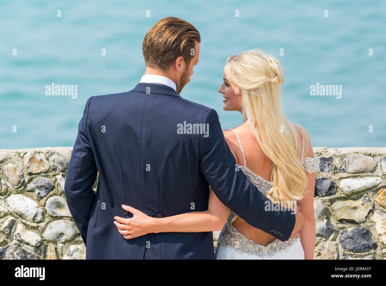 Bride and Groom on a beach having photos taken for their wedding day. Married couple. Getting married. Day of marriage. Stock Photo