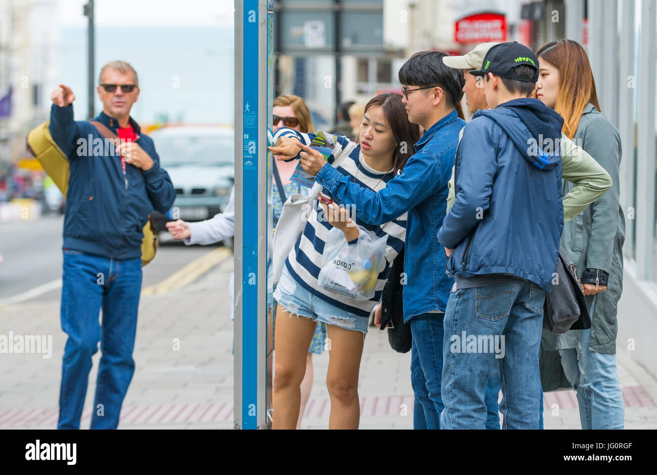japanese-tourists-looking-at-a-street-map-in-a-city-to-find-directions-JG0RGF.jpg