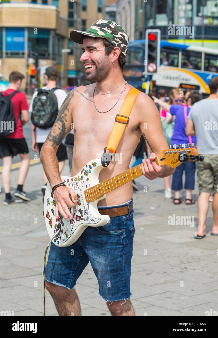 shirtless-busker-playing-guitar-on-a-hot-summers-day-in-a-busy-city-JGT656.jpg