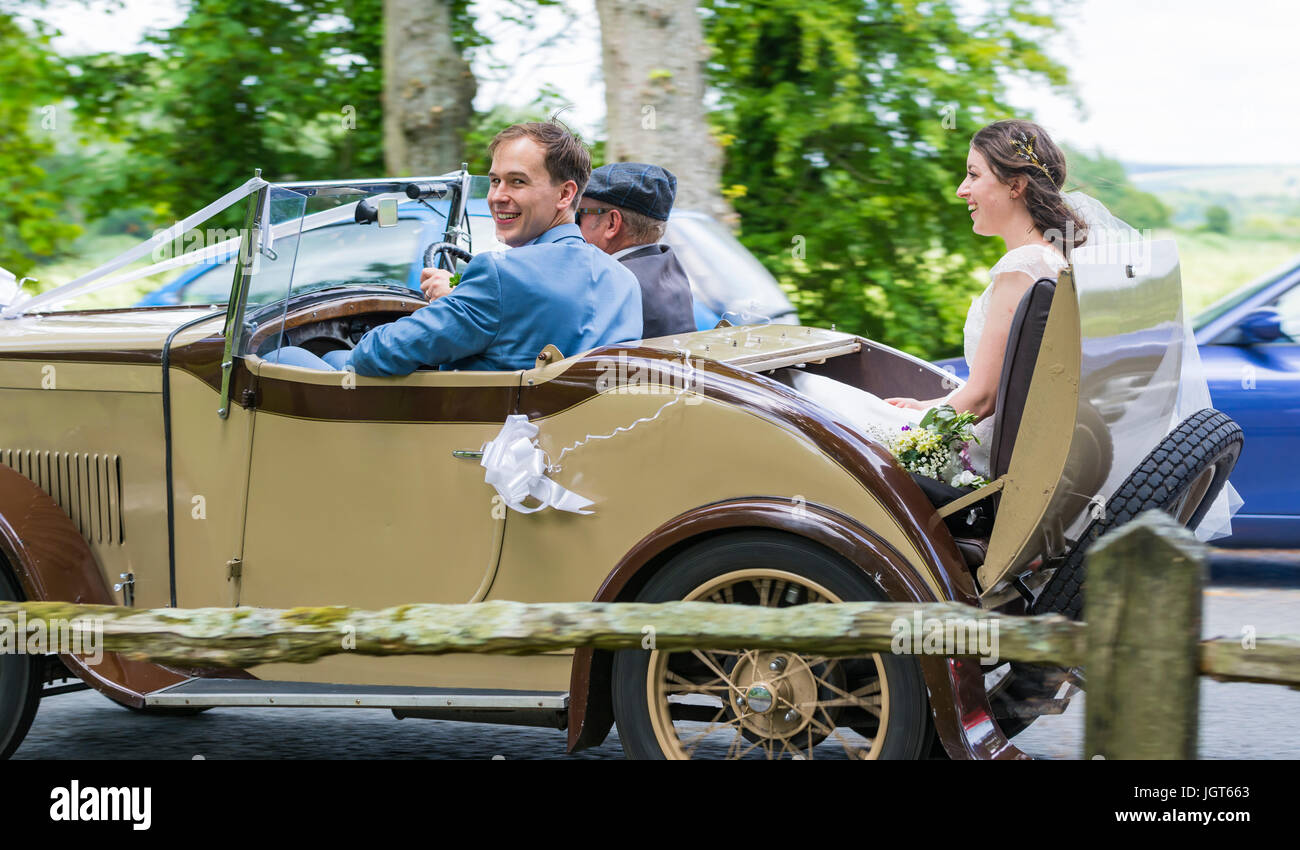 Bride and Groom travelling in an old car on their wedding day. Stock Photo