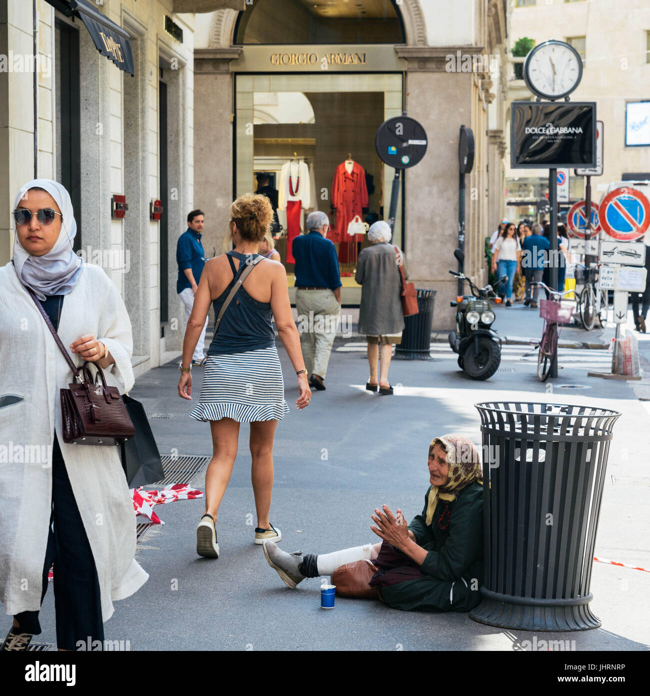 Milan, Italy - July 14th, Shoppers on Via Montenapoleone, one of Milan's high-end shopping districts, stroll past Stock Photo