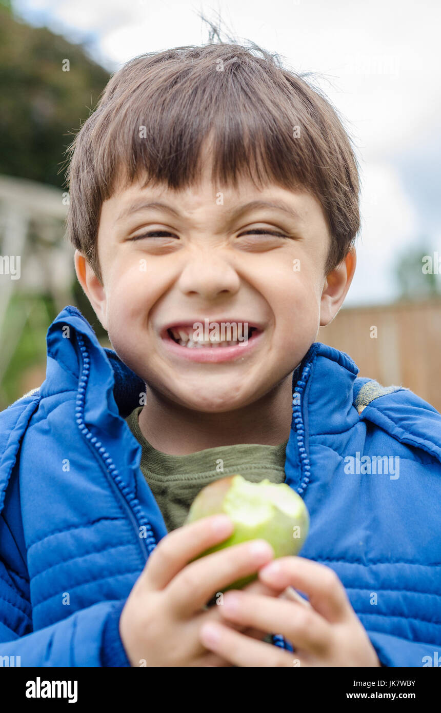 a-boy-eating-a-home-grown-apple-in-the-back-garden-JK7WBY.jpg