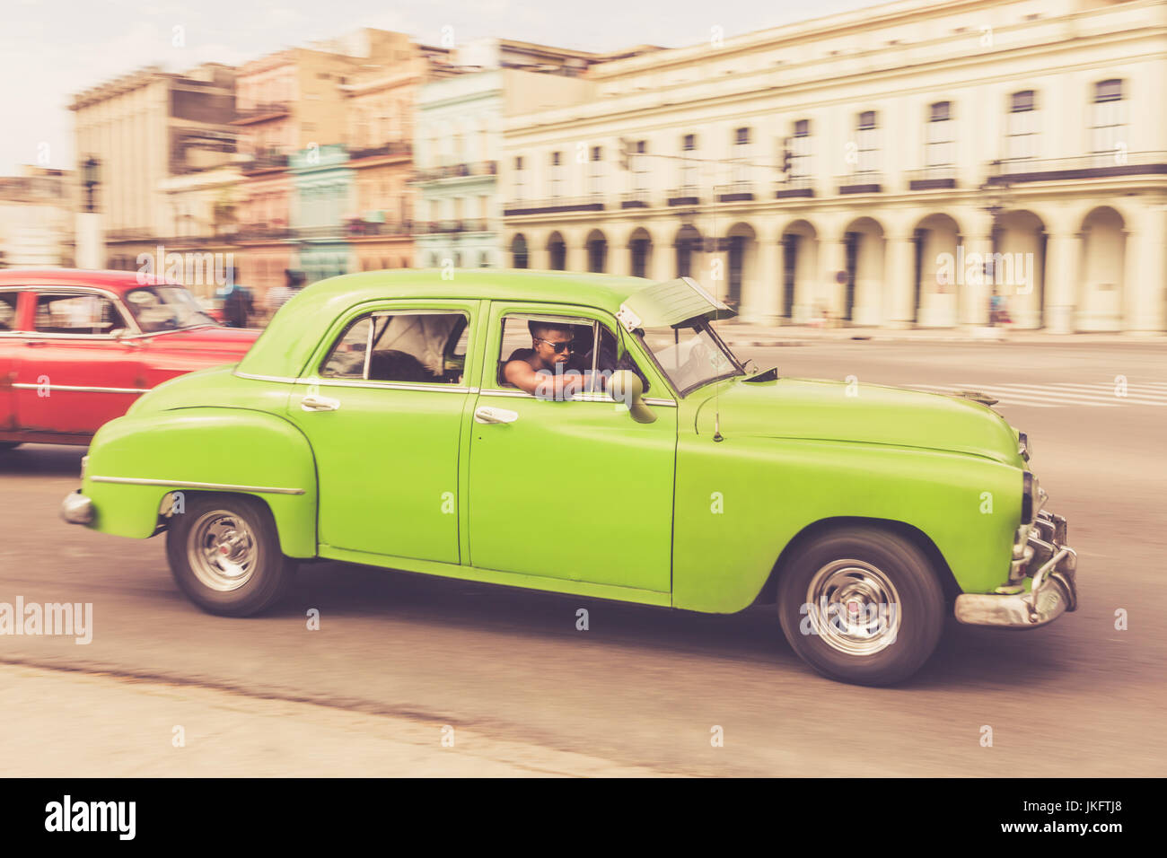 green-american-classic-car-with-young-cubans-driving-in-old-havana-JKFTJ8.jpg