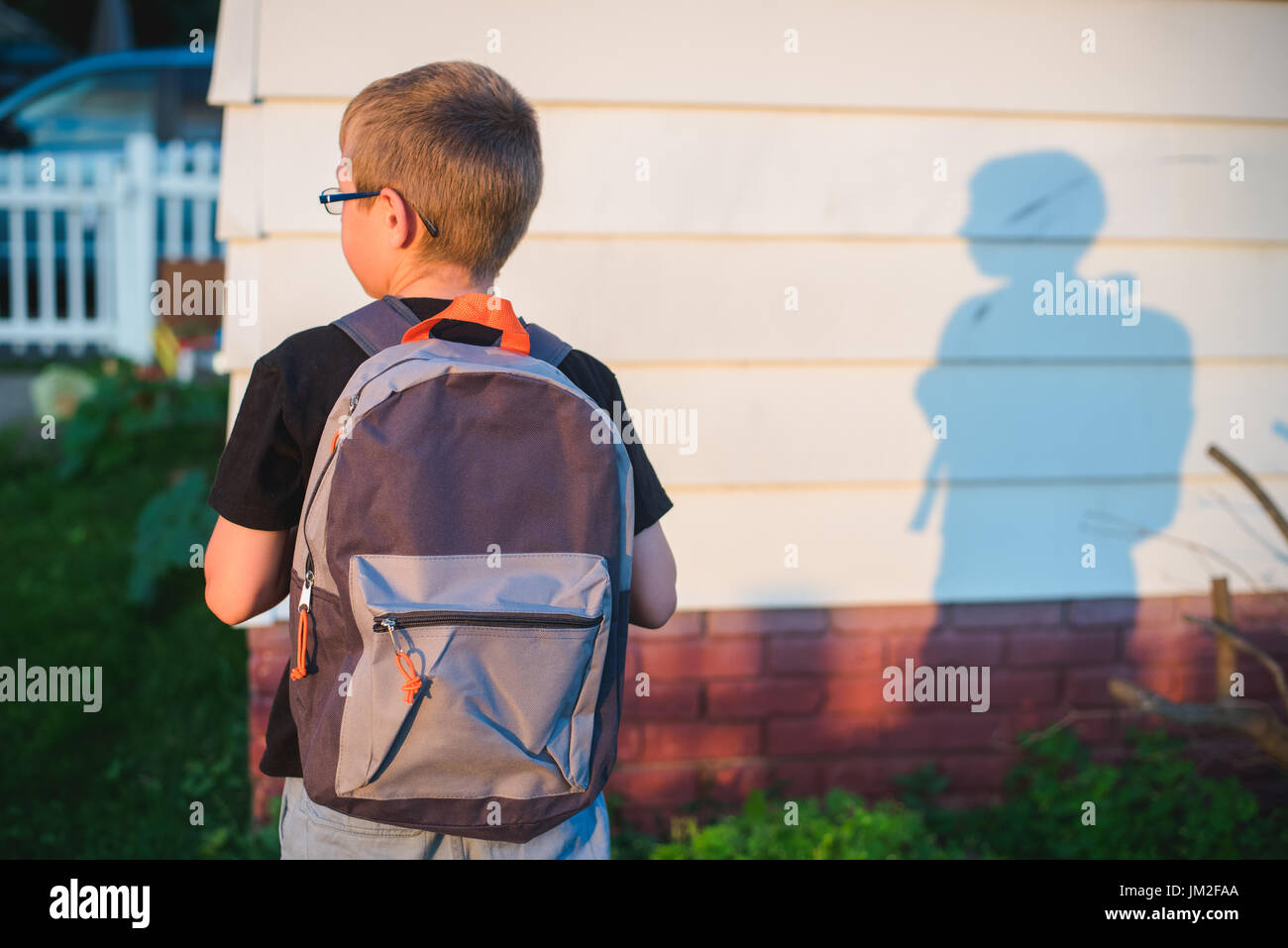 A student wearing a back pack or book bag and ready for school. - Stock Image