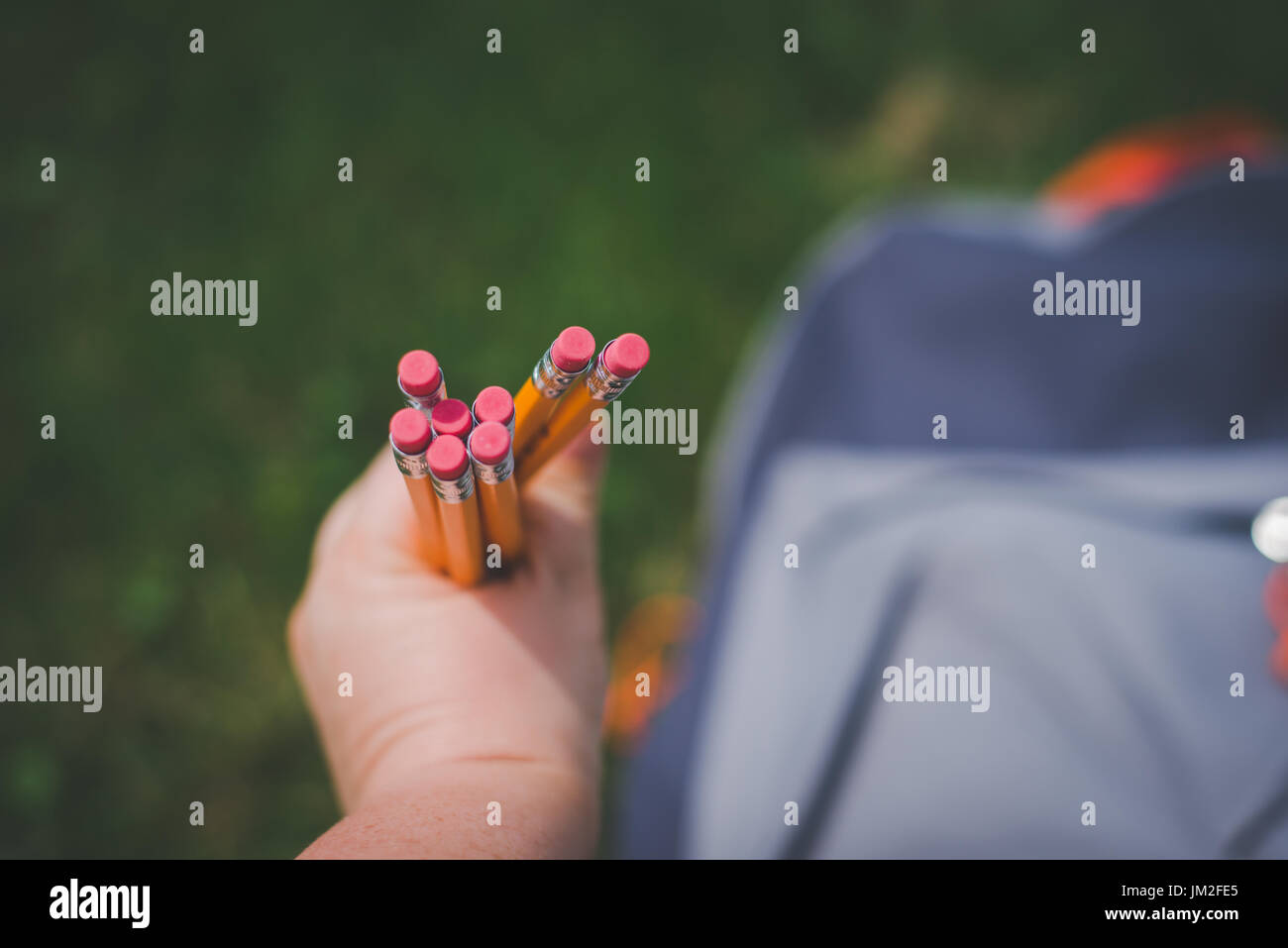 Hands holding school pencils with erasers. - Stock Image