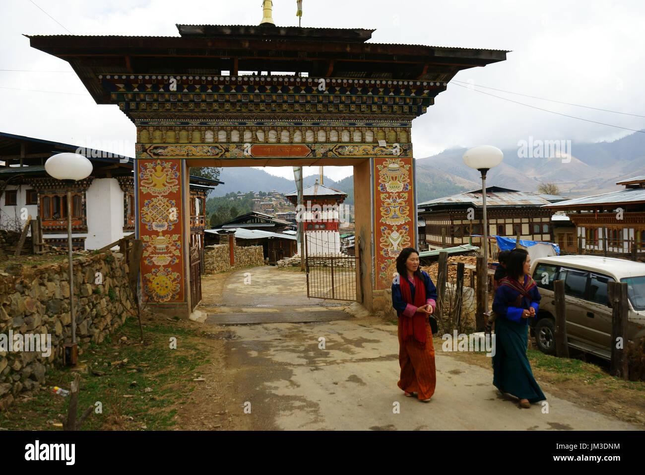 Women in traditional dress walking outside gate to the Gangtey monastery, Phobjikha valley Bhutan - Stock Image