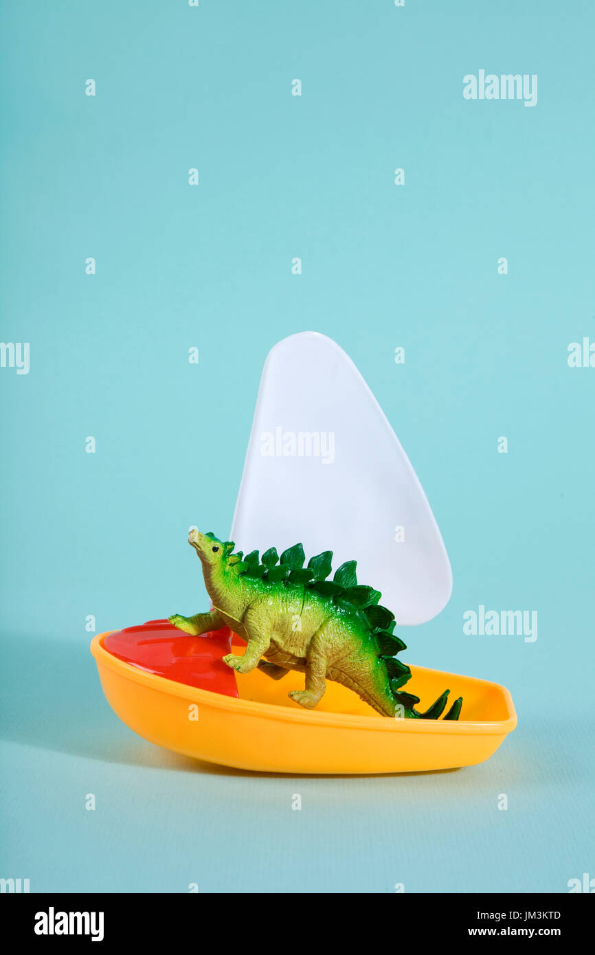 A dinosaur lost at sea on a toy boat like a noah's ark metaphor. Minimal Poetic still life photography - Stock Image