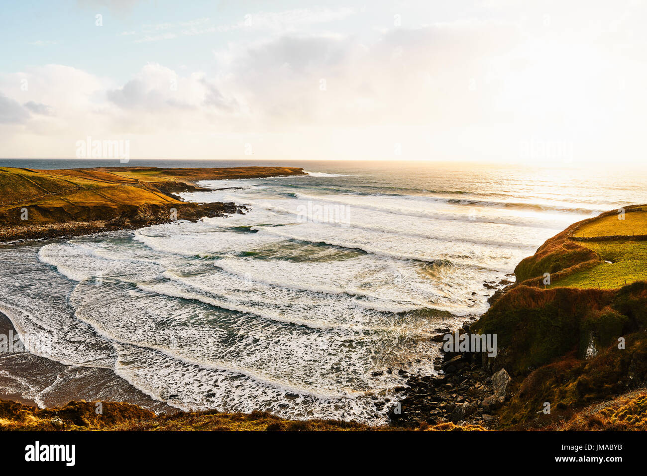 Irish beach during sunset in the summer with a blue sky and waves smashing against the rocks - Stock Image