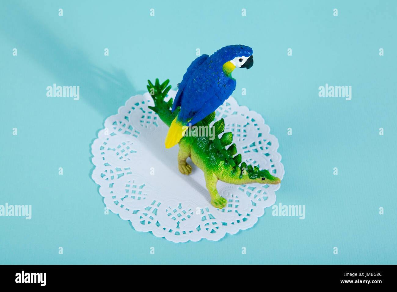 A dinosaur stegosaurus and a blue parrot on a white lace paper doily with a vibrant turquoise background. Minimal - Stock Image