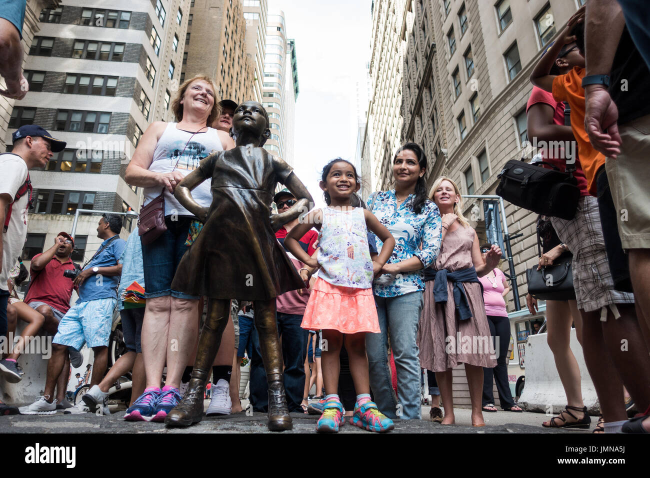 Young girl, with her family, posing at the front of the Fearless Girl bronze sculpture on Wall Street, NY - Stock Image