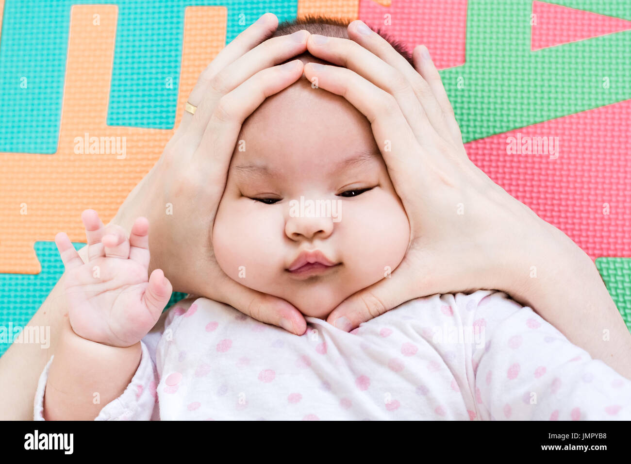 Hands of mother squeezing on face of her cute little baby on the eva foam in bedroom - Stock Image