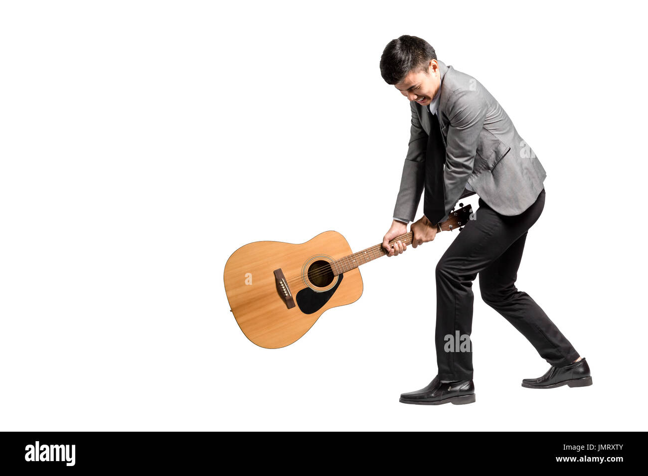 Portrait of a young business man smashing his guitar. Isolated on white background with copy space and clipping - Stock Image