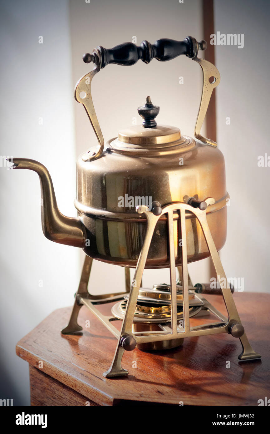 antique  copper kettle on stand - Stock Image