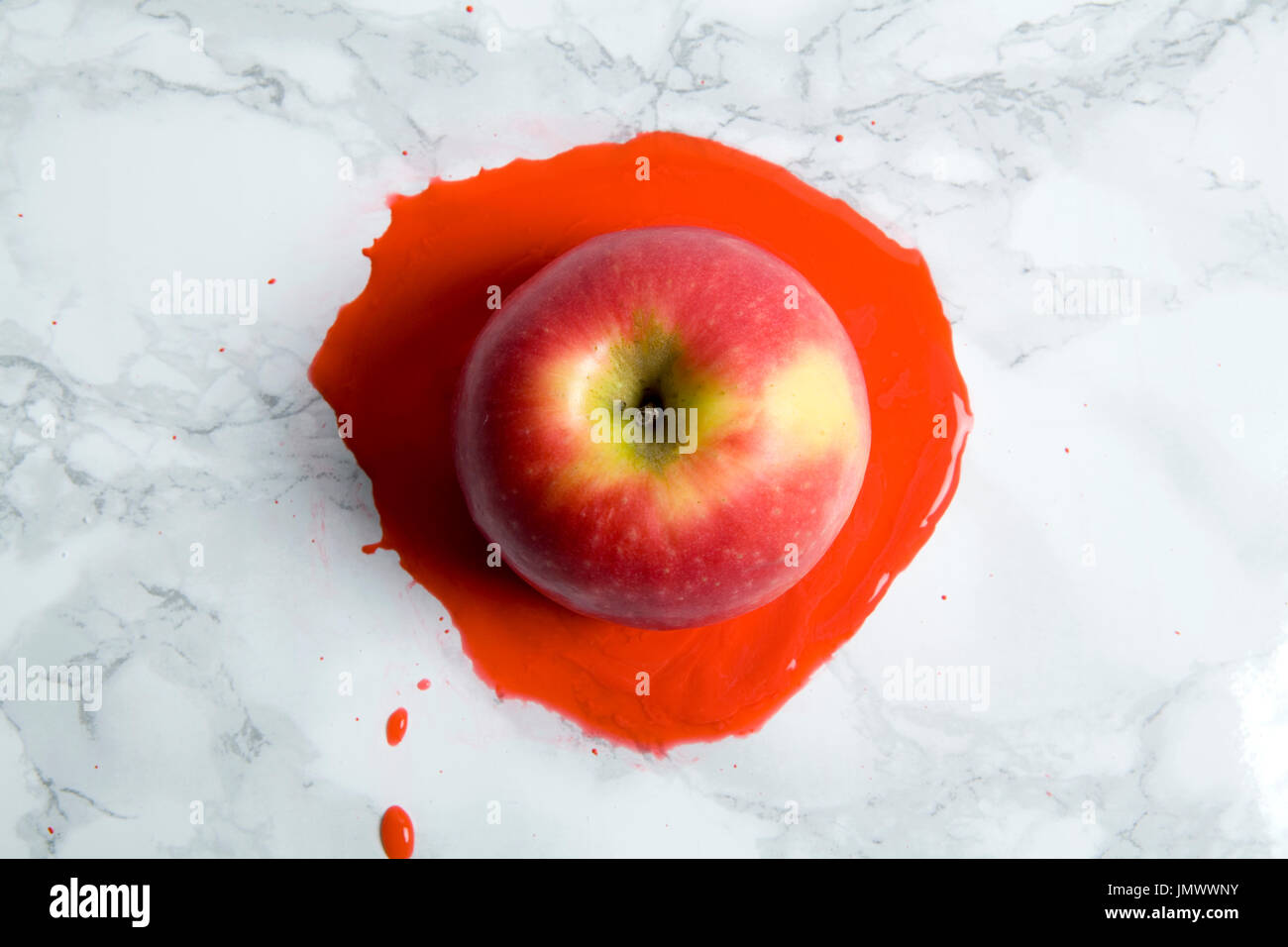 An apple melting on a marble background. minimal color still life photography - Stock Image