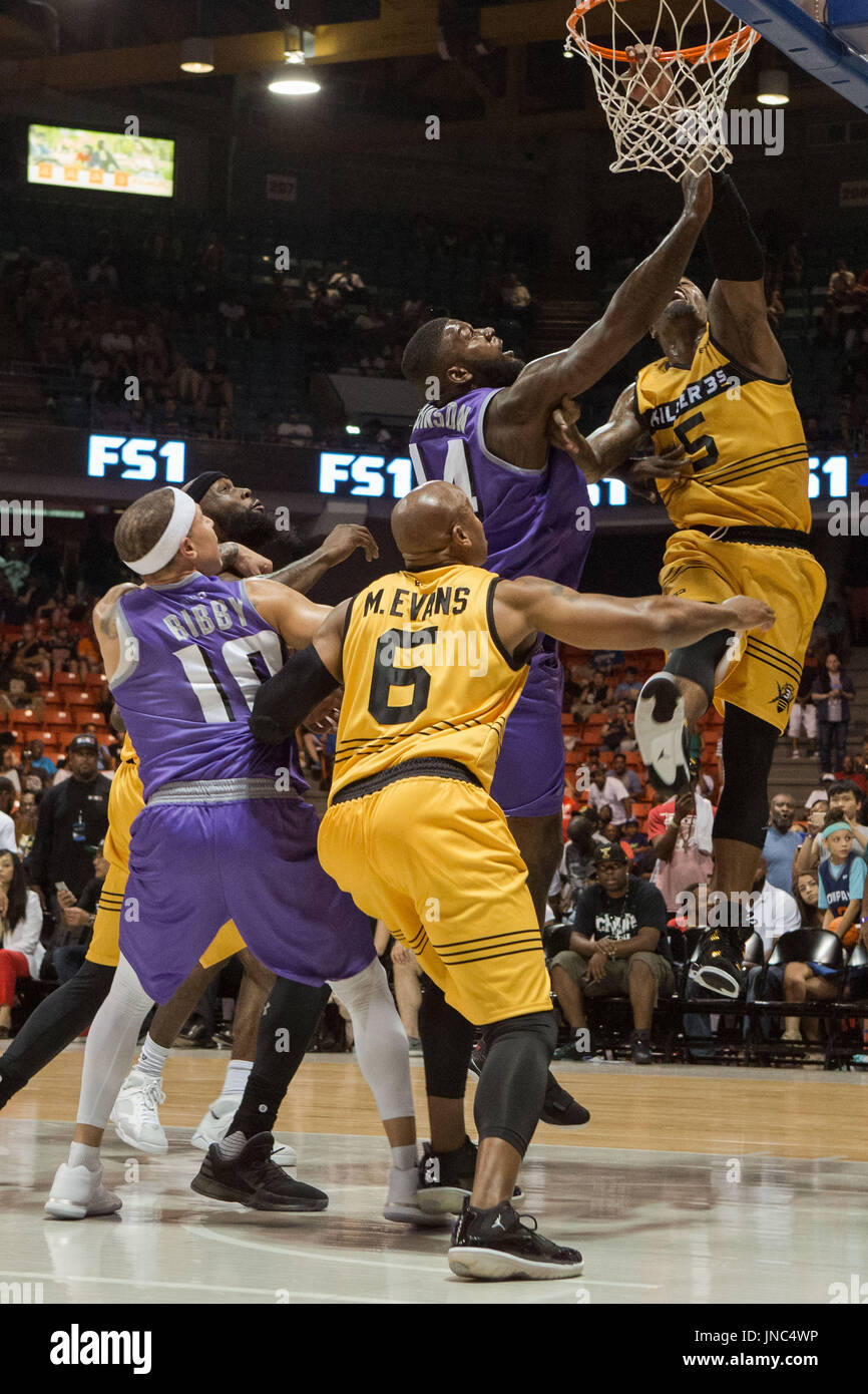 Stephen Jackson #5 Killer 3s jumps up takes shot hangs to rim one hand as Ivan Johnson #44 Ghost Ballers attempts - Stock Image