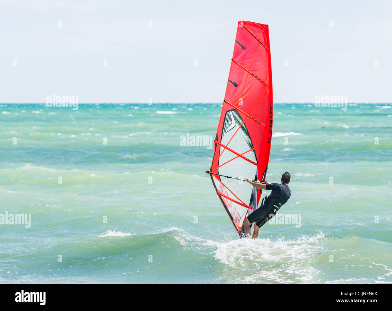 Man windsurfing on the sea on a windy day. - Stock Image