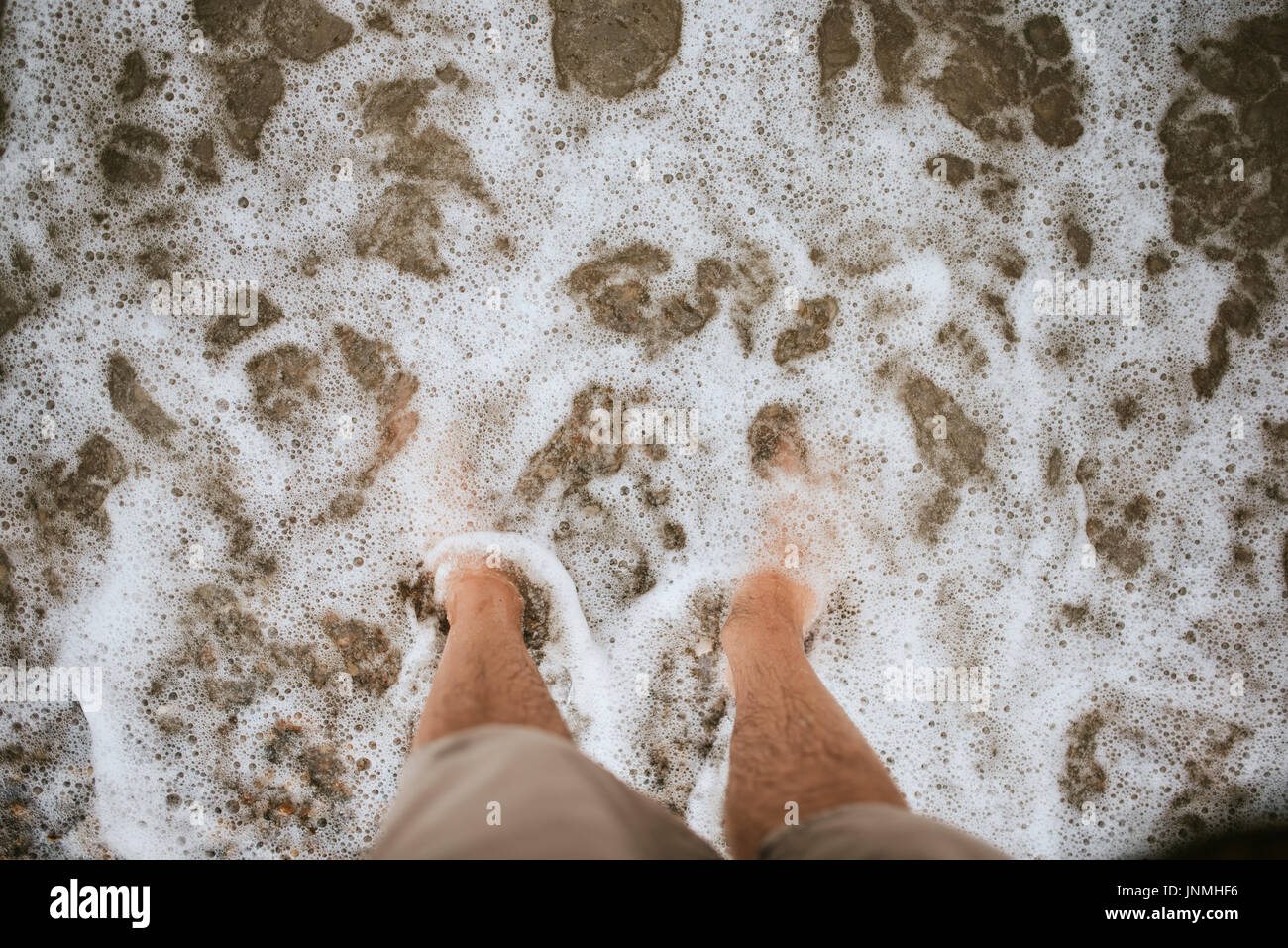 Bare feet on the beach covered with sea foam - Stock Image